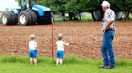 Toddlers by fence and tractor iStock-_cstar55_SMLL.jpg